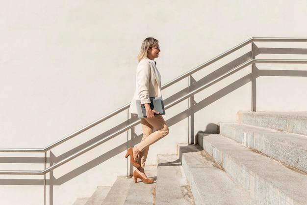 Donna piena del colpo che sale le scale Foto Gratuite