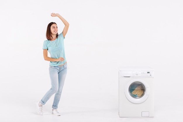 Full shot woman dancing near washing machine Free Photo