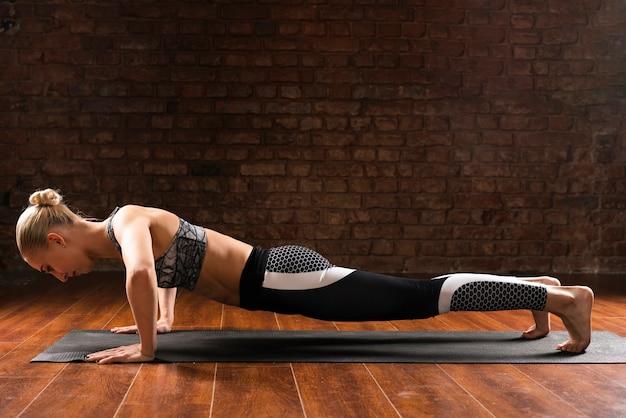 Full shot woman doing push-ups Free Photo