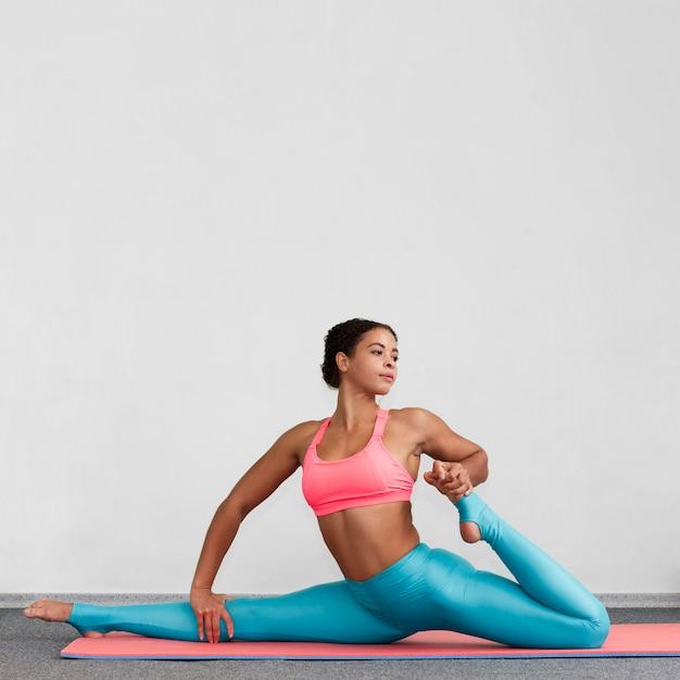 Full shot woman doing the splits on a mat Free Photo