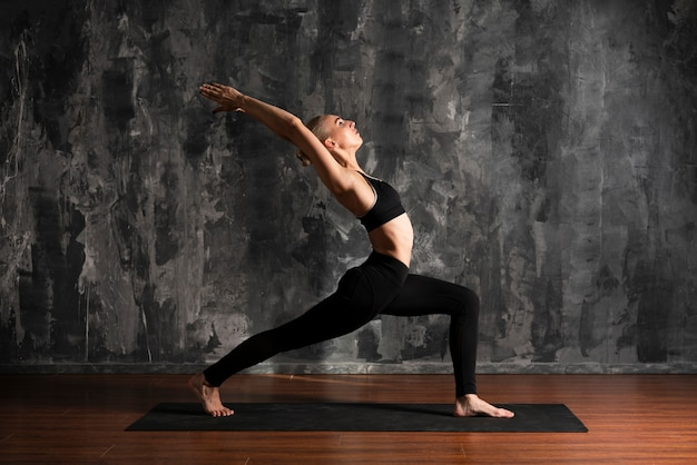 Full shot woman doing yoga on mat Free Photo