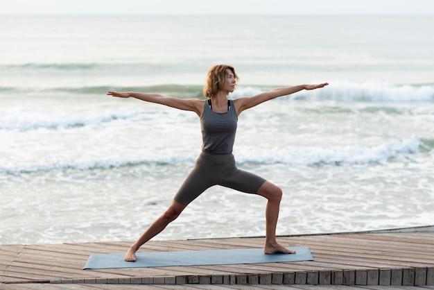 Full shot woman doing yoga pose near sea Free Photo