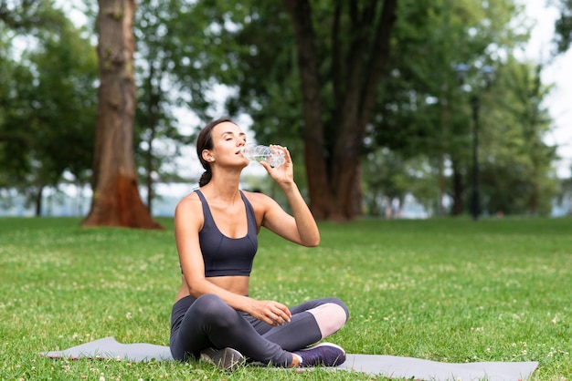 Full shot woman drinking water outdoors Free Photo