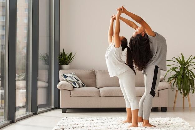 Colpo pieno donna e ragazza che fanno yoga Foto Gratuite