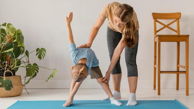 Полный снимок женщина помогает ребенку упражнения Бесплатные Фотографии