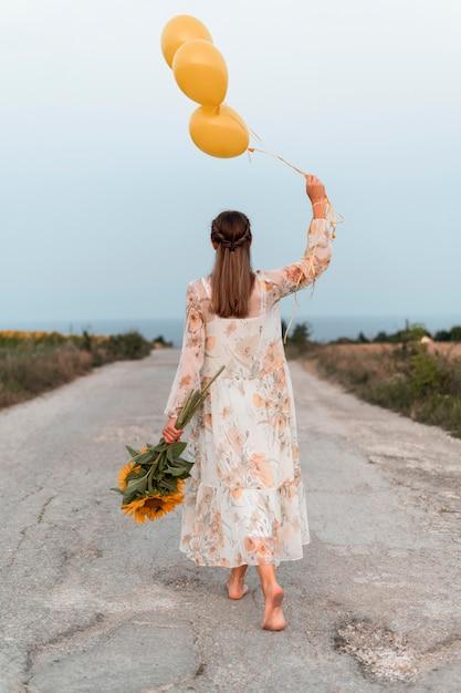風船と花を保持しているフルショットの女性 無料写真