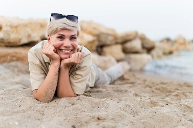 ビーチの上に敷設フルショットの女性 無料写真