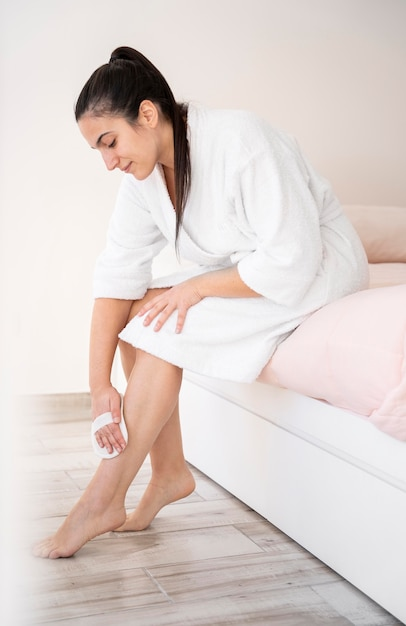 Donna piena del colpo che massaggia le gambe Foto Gratuite