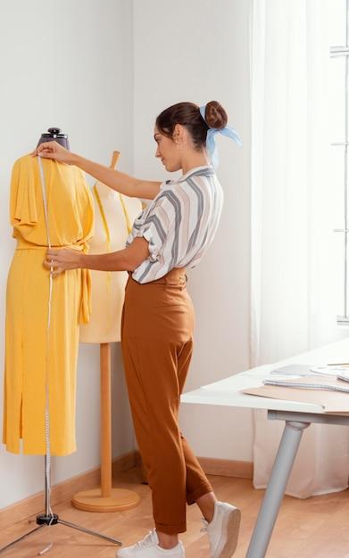 Vestito di misurazione della donna del colpo pieno Foto Gratuite