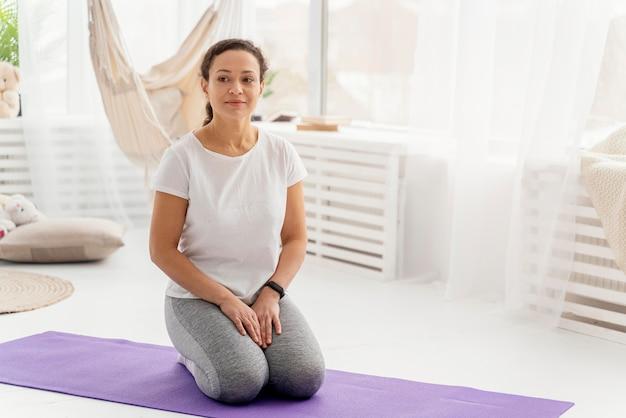 Женщина в полный рост на коврике для йоги Бесплатные Фотографии