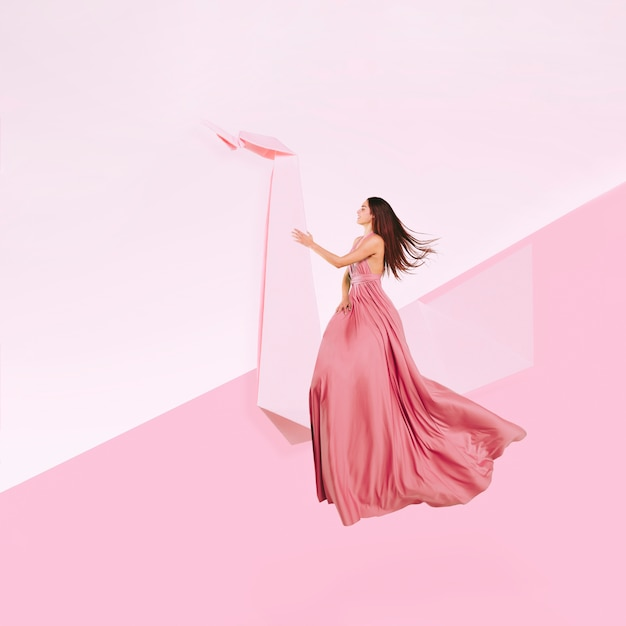 Full shot woman in pink dress levitating Free Photo