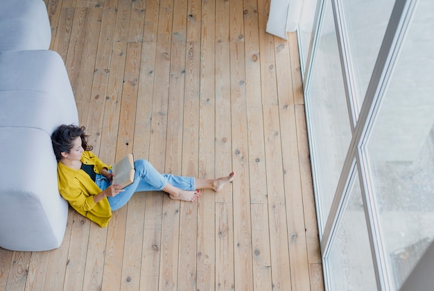 Full shot woman reading a book on the floor Free Photo