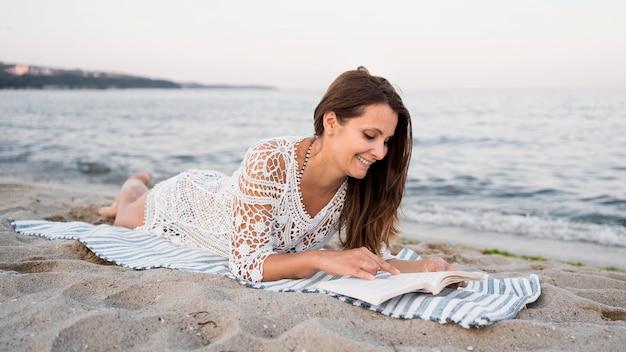 Полный выстрел женщина, читающая на одеяле Бесплатные Фотографии