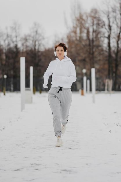 Полный выстрел женщина работает в снегу Бесплатные Фотографии