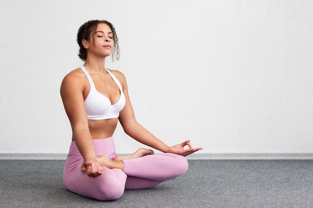 Full shot woman sitting in meditating position Free Photo