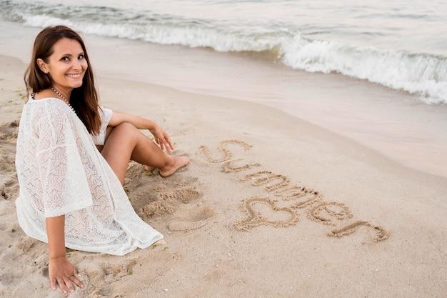 Полный выстрел женщина, сидящая на песке Бесплатные Фотографии
