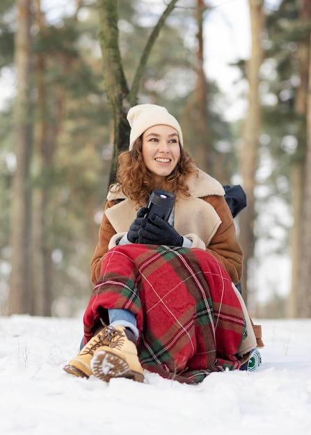 Полный выстрел женщина, сидящая на снегу Бесплатные Фотографии