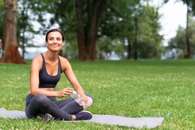 Full shot woman sitting on yoga mat Free Photo