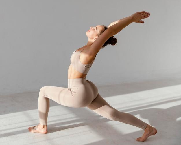 Full shot woman stretching indoors Free Photo
