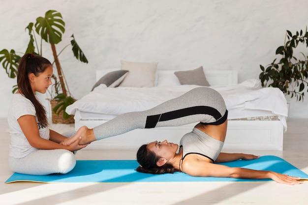 Donna del colpo completo che allunga sulla stuoia di yoga Foto Gratuite