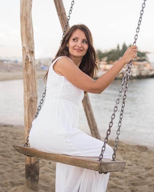 Женщина в полный рост качается на пляже Premium Фотографии