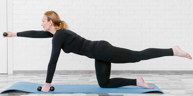 ヨガマットでトレーニングするフルショットの女性 無料写真