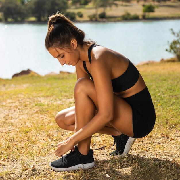Женщина в полный рост, завязывающая шнурки Бесплатные Фотографии