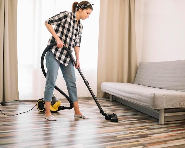 掃除機をかけるフルショットの女性 無料写真