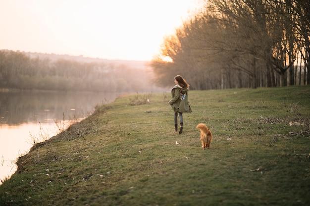 Полный выстрел женщина гуляет с собакой Premium Фотографии