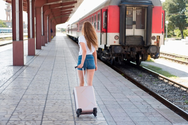 Full shot woman walking with luggage in train station Free Photo