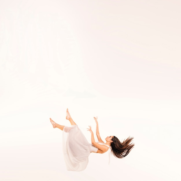 Full shot woman in white dress floating Free Photo