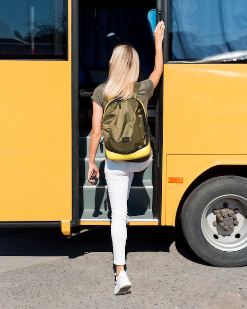 Full shot woman with backpack getting on bus Free Photo