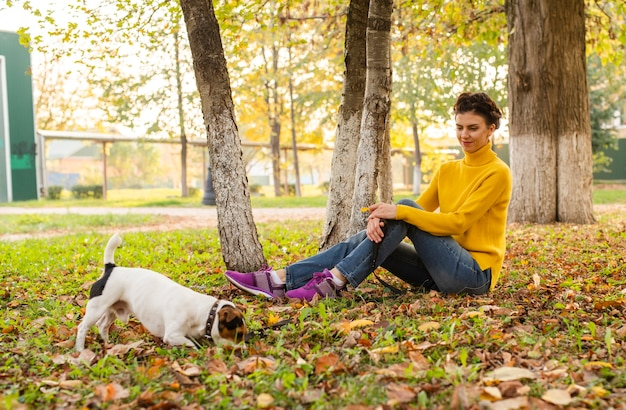 Full shot woman with her dog in the park Free Photo