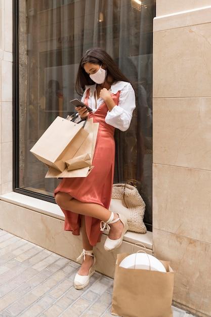 Colpo completo di donna con borse della spesa e smartphone Foto Gratuite