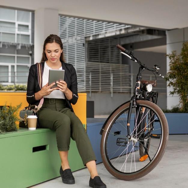 Donna del colpo pieno con tablet e bici Foto Gratuite