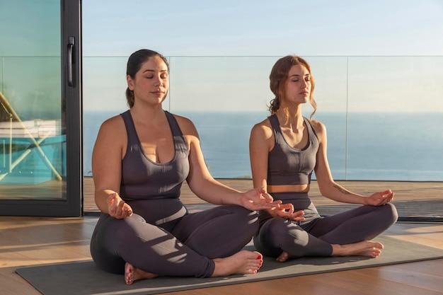 Full shot women meditating together Free Photo