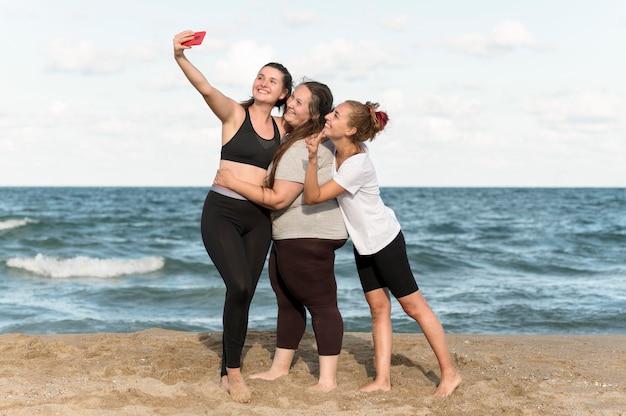 海辺でselfiesを取るフルショットの女性 無料写真