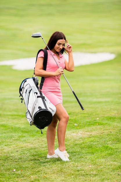 Full shot young woman with golf clubs Free Photo