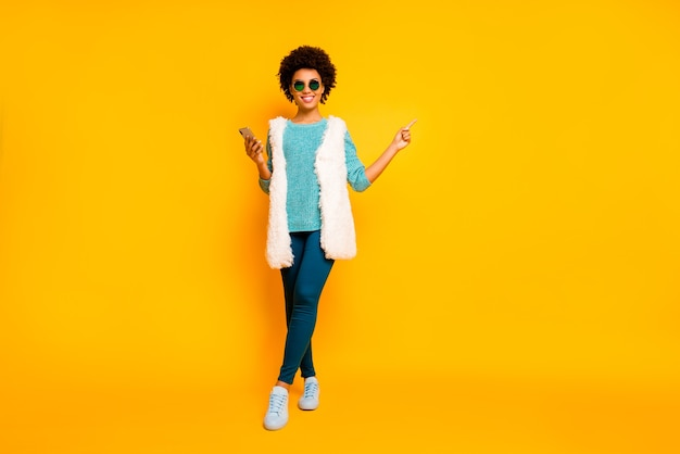 Full size photo positive afro american girl use smartphone browse promo point finger copyspace wear blue pants trousers teal jumper white vest stylish trendy isolated yellow color wall Premium Photo