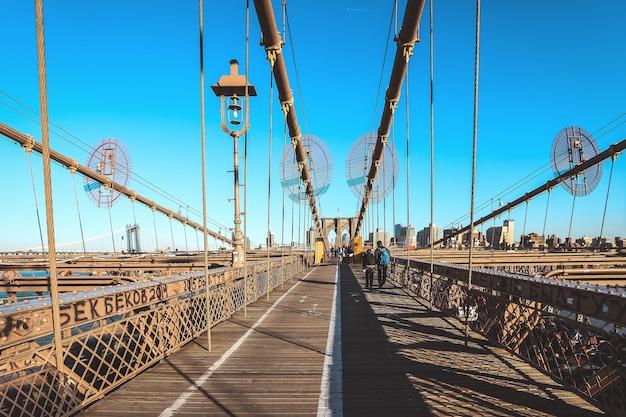 Full of tourist walking on brooklyn bridge in a beautiful day, new york Premium Photo
