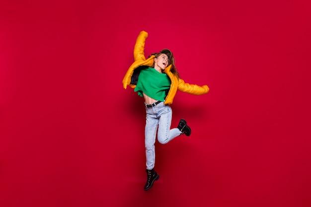 黄色のジャケットと赤の緑のセーターでジャンプする幸せな興奮した女の子の完全な長さ 無料写真