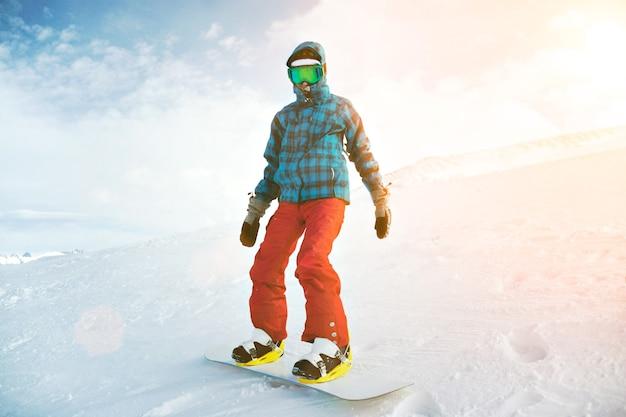 完全装備で、寒い初心者のスノーボーダーから覆われています。グーグルマスクを着用し、裏側の端にあるスキー場の上部に立っています。 無料写真