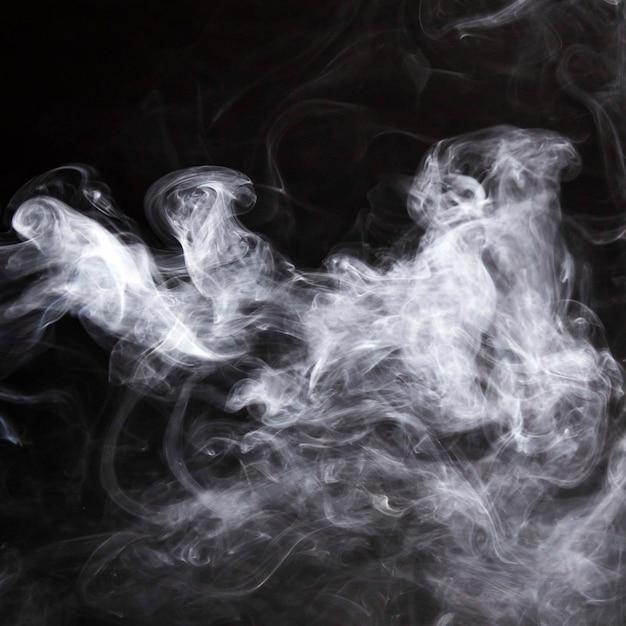 Пары дыма распространяются на черном фоне Бесплатные Фотографии