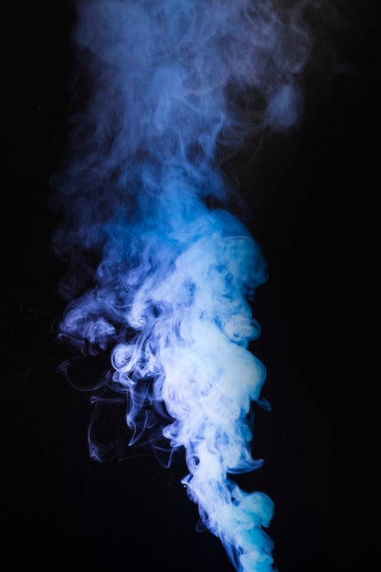 Fumes of purple smoke at the center of the black backdrop Free Photo