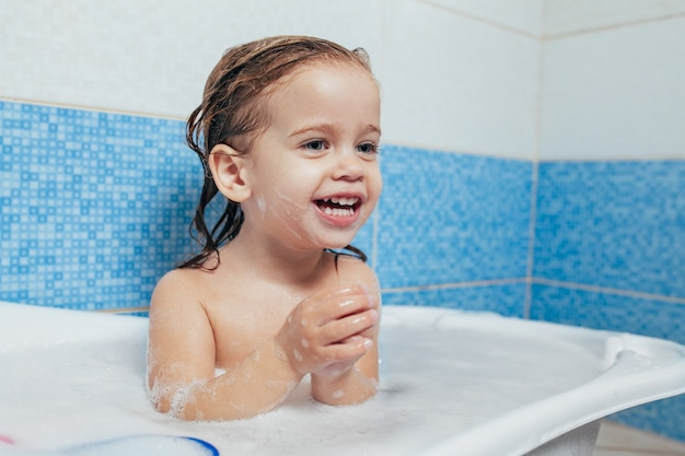 Fun cheerful happy toddler baby taking a bath playing with foam bubbles. Premium Photo
