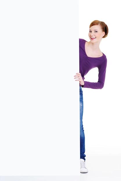 La donna sorridente divertente guarda fuori a causa di un banner pubblicitario Foto Gratuite