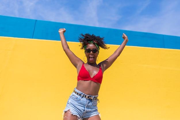 Fun молодая афро американская женщина смеется с поднятыми руками Premium Фотографии