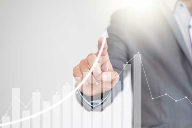 Fund manager hand writing increasing graph to screen monitor Premium Photo