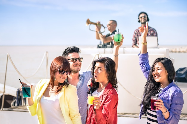 Funky people dancing music and having fun together at beach rave afterhour party Premium Photo
