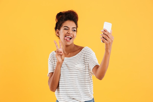 Funny african lady grimacing and making selfie on phone isolated Free Photo